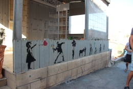 Stenciled images from Banksy line a fence