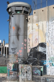 A recent addition to the wall shows President Trump holding up one of the towers in response to his planned wall with Mexico.